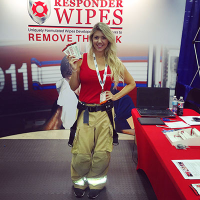 Demonstrating fire decontamination wipes at a firefighter conference