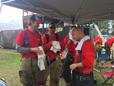 Firefighters using extra large decontamination wipes